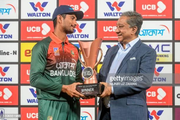 Bangladesh's team captain Mahmudullah poses for photographs along with Bangladesh Cricket Board president Nazmul Hasan Papon as he receives the...