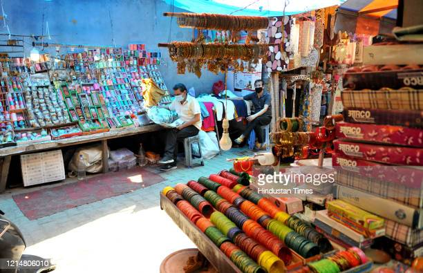 Bangle vendor reads a paper while wating for customers after opening his shop ahead of Eid ul-Fitr following a prolonged closure, on May 23, 2020 in...