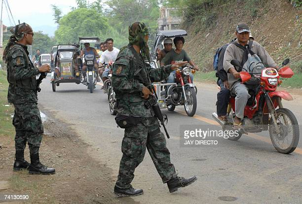 Special action force policemen armed with automatic rifles inspect commuters crossing a road block in Bangued in the northern Philippine province of...