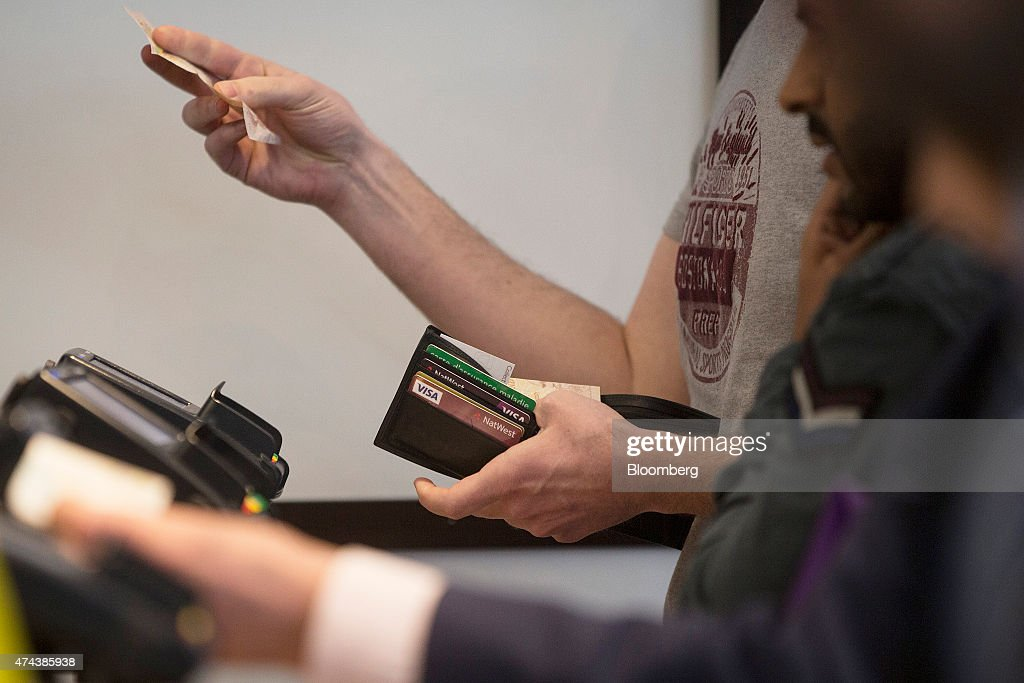 Bank and Visa Inc. credit cards are seen in a man's wallet as he pays with cash using a British banknote at a restaurant in London, U.K., on Friday, May 22, 2015. Credit and debit cards that can be used by tapping the reader are gaining users, and mobile apps are set to further boost the popularity of contactless paying. Photographer: Simon Dawson/Bloomberg via Getty Images