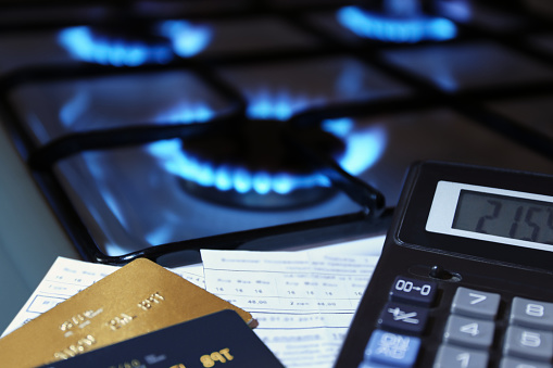 bank cards and a calculator on the background of a gas stove 1067008230