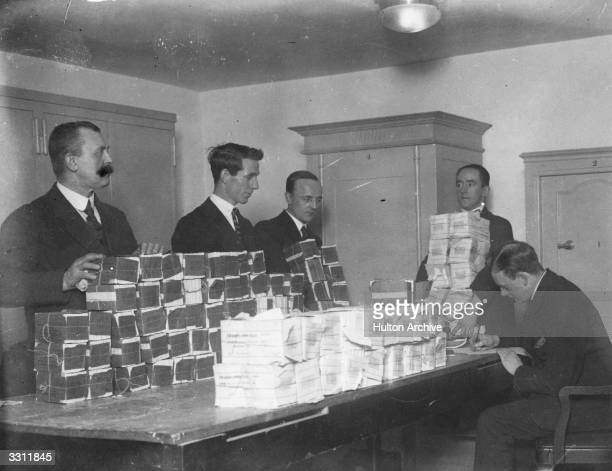 Bank cashiers in Cologne stacking millions of marks in the strong room in readiness for distribution to the customers upstairs February 1923