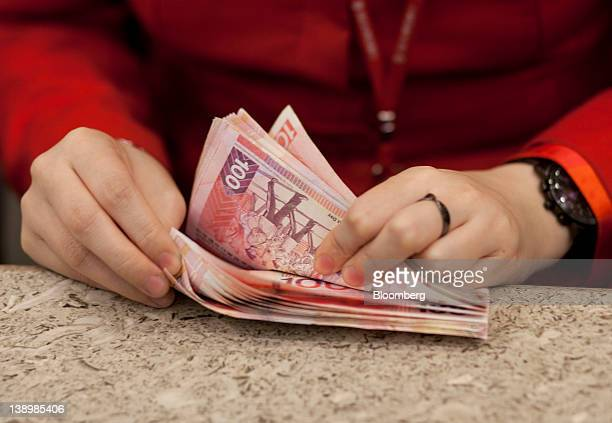 A bank clerk counts 100 dollar Hong Kong banknotes in an arranged photograph in the Bank of East Asia Ltd main branch in Hong Kong China on Wednesday...