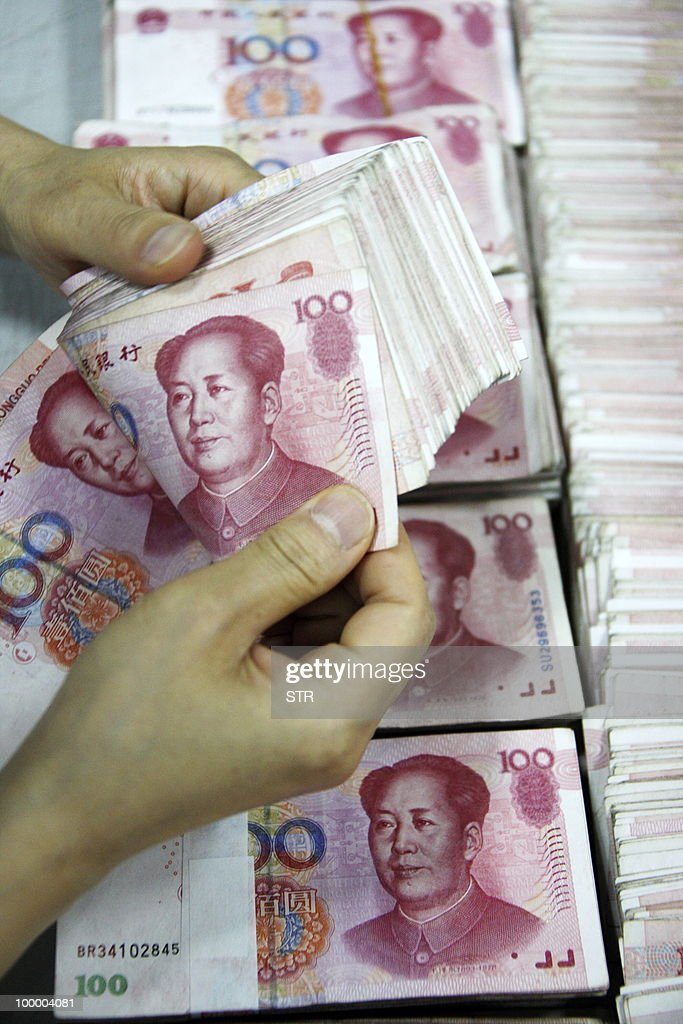 A bank clerk counts a stack of 100 yuan notes at a bank in Huaibei, east China's Anhui province on May 20, 2010. China stood firm against outside pressure to revalue its currency on May 20 ahead of key talks with the US, and reiterated its concerns about soaring US debt levels. CHINA