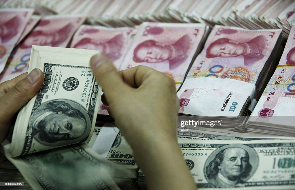 A bank clerk counts a stack of USD together with stacks of 100 yuan notes at a bank in Huaibei, east China's Anhui province on May 20, 2010. China stood firm against outside pressure to revalue its currency on May 20 ahead of key talks with the US, and reiterated its concerns about soaring US debt levels. CHINA