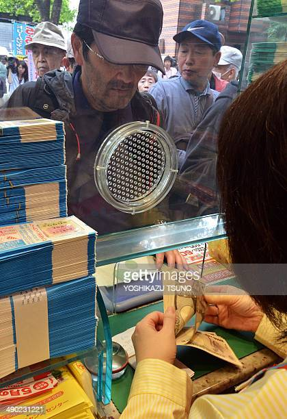 """Bank clerk counts bank notes as a customer purchases tickets for the 550 million yen """"Dream Jumbo Lottery"""" as the first tickets go on sale in Tokyo..."""