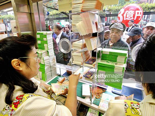 A bank clerk counts lottery tickets of the 300 million yen Yearend Jumbo Lottery at a Tokyo ticket booth 25 November 2005 Thousands of punters queued...