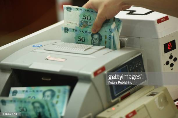 Bank clerk counts the fifth edition of renminbi banknotes during its debut at a bank outlet in Hangzhou in east China's Zhejiang province Friday,...