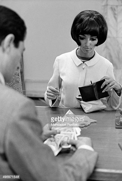 A bank clerk giving money to a woman 1966