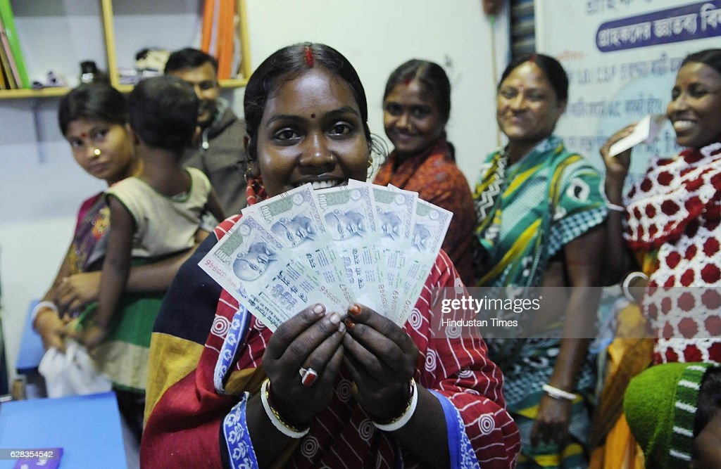 A bank customer is showing 100 rupee notes as she was waiting since midnight at SBI customer service point, Laxbagan, Satjelia island on December 5, 2016 Sunderban, India. Since demonetization, a total of 1156 CSPs in rural areas has helped customers for cash transaction through their accounts. Rural areas are also being served with channel of bank Business Correspondent.