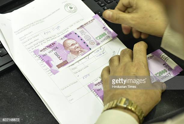 A bank employee at an exchange counter for old currency at Allahabad Bank branch of Parliament Street on November 10 2016 in New Delhi India It was a...