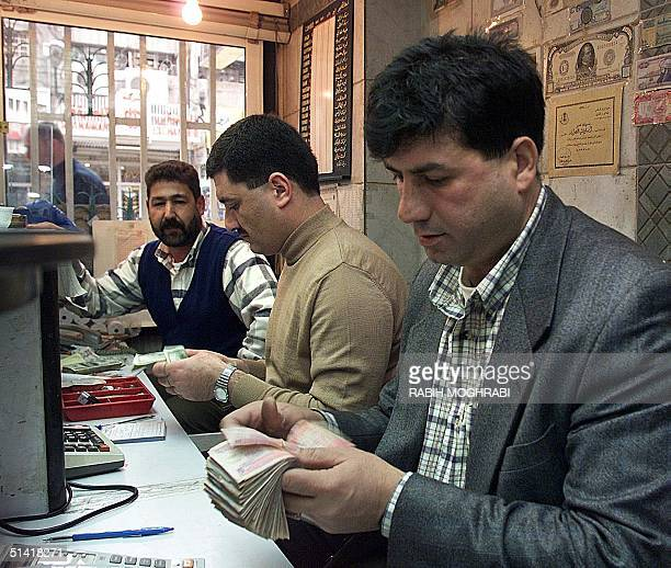 A bank employee counts money 07 February in Amman where the Jordanian dinar has plunged since King Hussein's return from the US last week following...