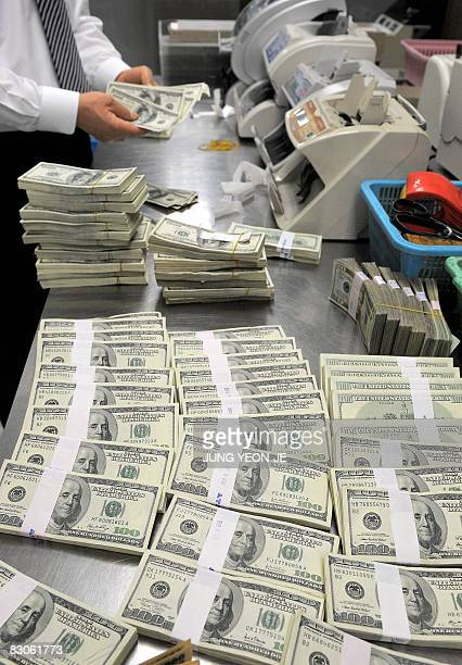 A bank employee counts US dollar notes at the Korean Exchange Bank in Seoul on September 30 2008 The South Korean currency the won tumbled against...