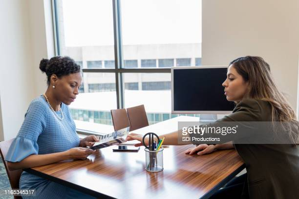 bank employee discusses bank services with customer - pamphlet stock pictures, royalty-free photos & images