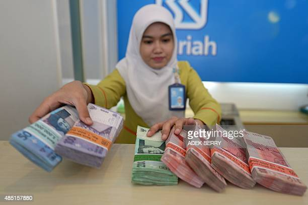 A bank employee displays bundles of Indonesian rupiah bank notes in Jakarta on August 25 2015 Asian shares were mixed after a seesaw session on...