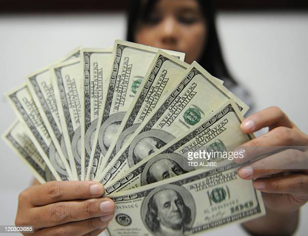 A bank employee displays US dollar notes in Manila on August 3 2011Philippine President Benigno Aquino said August 3 the US dollar's weakness could...