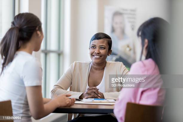 bank employee meets with mom and daughter - bank manager stock pictures, royalty-free photos & images