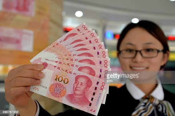Bank employee shows new 100-yuan banknotes in Handan, north China's Hebei province on November 12, 2015. China on November 12 put into circulation a...