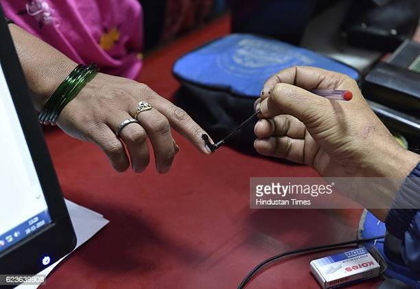 Bank employees marking customers exchanging defunct currency notes with indelible ink in a bid to tackle long queues and chaos in banks and ATMs at...