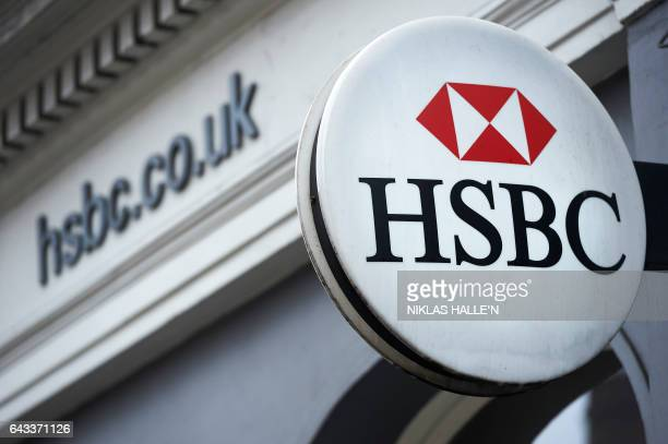 A HSBC bank logo is seen on a sign outside a branch of the bank in central London on February 21 2017 HSBC profits plunged last year on huge...