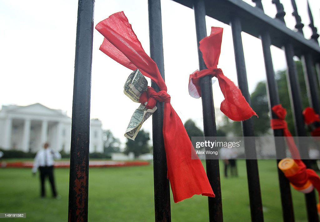 Bank notes and prescription drug bottles were tied on the White House fence by activists who participate in a civil disobedience outside the White House after a march from the Washington Convention Center July 24, 2012 in Washington, DC. AIDS activists from organizations all around the world participated in the march to 'demand rights and resources to confront and cure HIV/AIDS.'