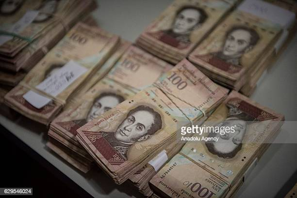 Bank Notes of 100 Bolivares are displayed over a counter in a spare part business in Los Teques on December 13 2016 Venezuelan President Nicolas...