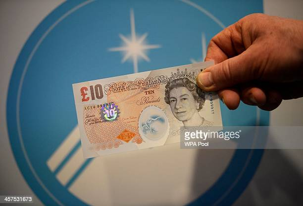 Bank of England employee shows off an example of a new polymer banknote with it's distinctive seethrough ring after a news conference with Governor...