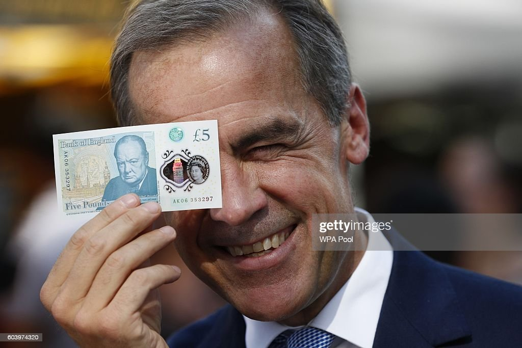 Bank of England governor Mark Carney poses with a new polymer five pound note at Whitecross Street Market on September 13, 2016 in London, United Kingdom. The new plastic note is designed to be more durable and features a portrait of former British Prime Minister Sir Winston Churchill.
