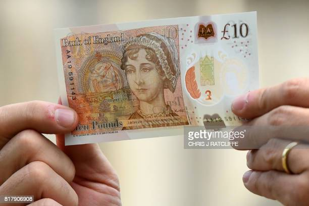 Bank of England Governor Mark Carney poses with one of the central bank's new ten pound notes featuring author Jane Austen duting its launch at...