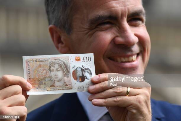 Bank of England Governor Mark Carney poses with one of the central bank's new ten pound notes featuring British author Jane Austen during its...