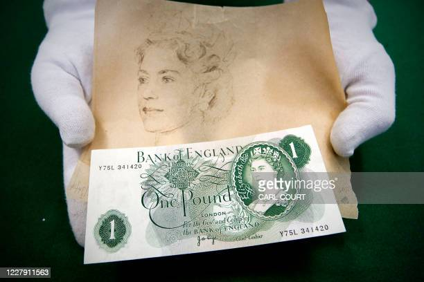 A Bank of England Museum employee holds an original draught sketch of Britain's Queen Elizabeth II and the original GBP 1 bank note on which the...