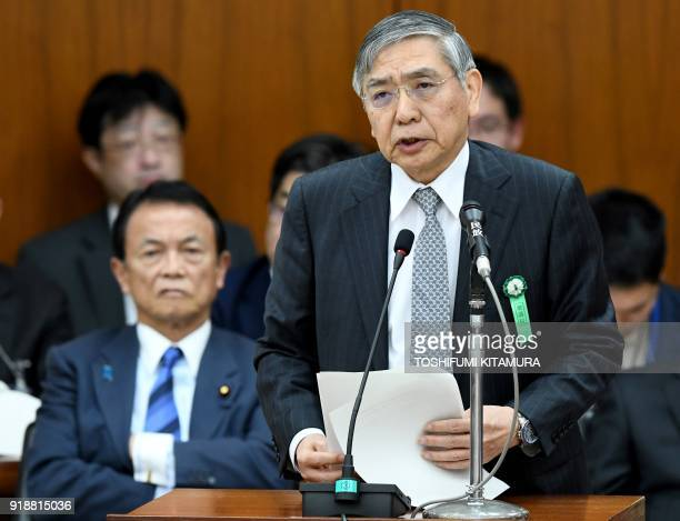Bank of Japan governor Haruhiko Kuroda answers a question beside Japan's Finance Minister Taro Aso while attending a financial committee meeting of...