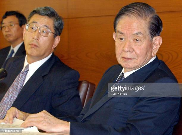 Bank of Japan Governor Masaru Hayami and Director Takahiro Mitani listen to the questions from reporters during a press conference at its...