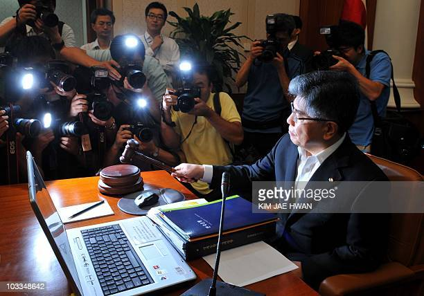 Bank of Korea Governor Kim ChoongSoo bangs a gavel before he presides over the Monetary Policy Committee meeting at the central bank in Seoul on...