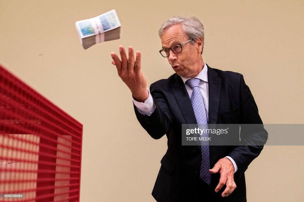 Bank of Norway's Director, Oystein Olsen, throws old 200 krone notes into a shredder at Bank of Norway's headquarter in Oslo, Norway, on May 16, 2018. - The old series of the Norwegian 100-krone and 200-krone notes will no longer be legal after May 30 2018. (Photo by Tore MEEK / NTB Scanpix / AFP) / Norway OUT