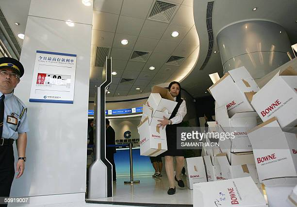 Bank staff clean up boxes of copies of the prospectus for the Initial Public Offering of China Construction Bank at a branch in Hong Kong 14 October...