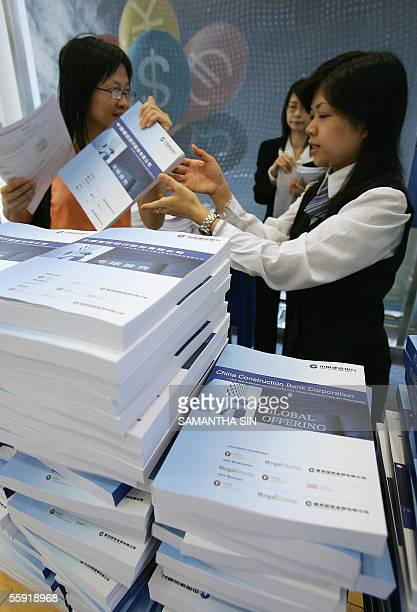 Bank staff distribute copies of the prospectus for the Initial Public Offering of China Construction Bank in Hong Kong, 14 October 2005. The CCB is...