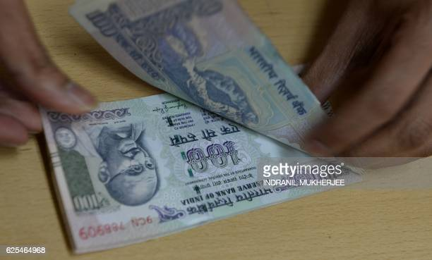 A bank staff member counts Indian 100 rupee notes to give to customers on November 24 in the wake of the demonetisation of old 500 and 1000 rupee...