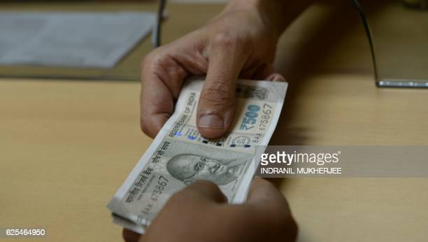 A bank staff member hands Indian 500 rupee notes to a customer on November 24 in the wake of the demonetisation of old 500 and 1000 rupee notes in...