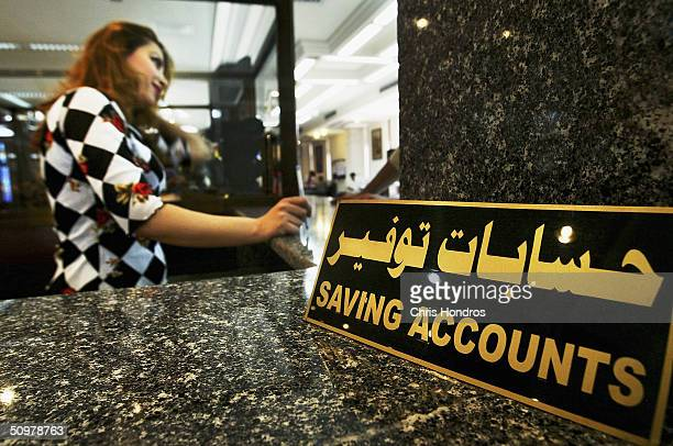 A bank teller at the Bank of Baghdad in the capital's Karrada neighborhood works with customers in the savings accounts department on June 20 2004 in...