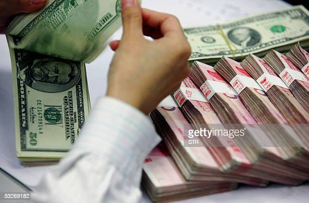 A bank teller counts the stack of Chinese yuan and US dollars at a bank in Shanghai 22 July 2005 China's cautious revaluation of its yuan is set to...