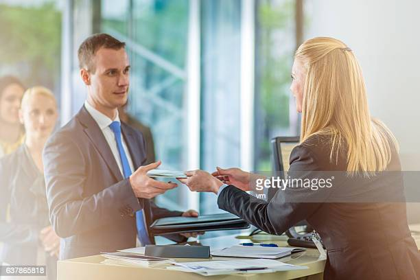 Bank teller giving document to a customer