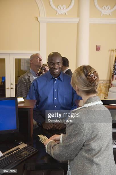 Bank teller making change for smiling man