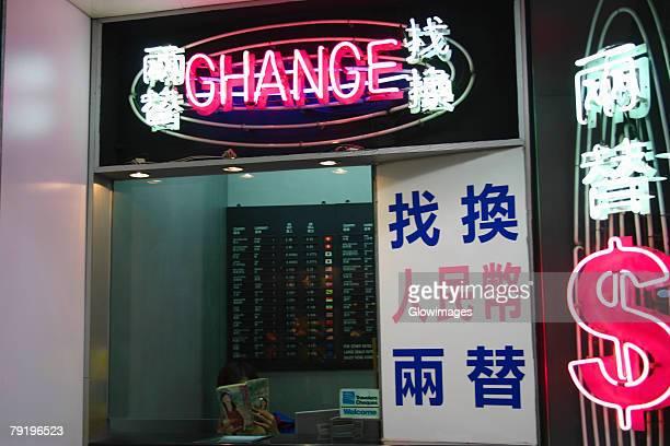Bank teller reading a book in a bank, Kowloon, Hong Kong, China