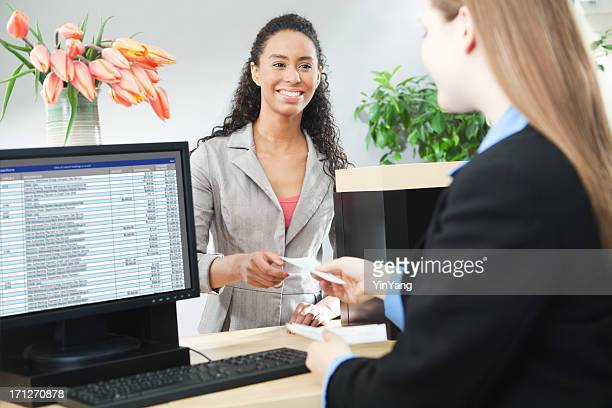 Bank Teller Servicing Banking Customer Transaction Over Retail Counter