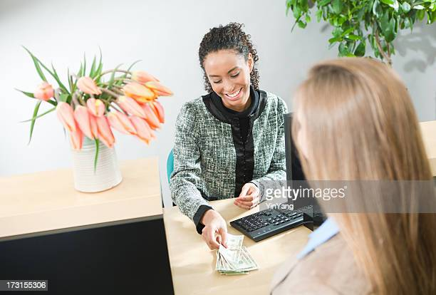 bank teller serving customer, currency transaction at retail banking counter - cashier stock pictures, royalty-free photos & images