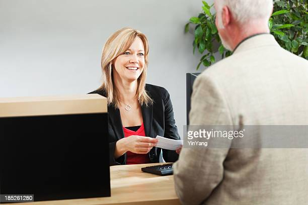 bank teller serving customer over retail banking service counter - cashier stock pictures, royalty-free photos & images