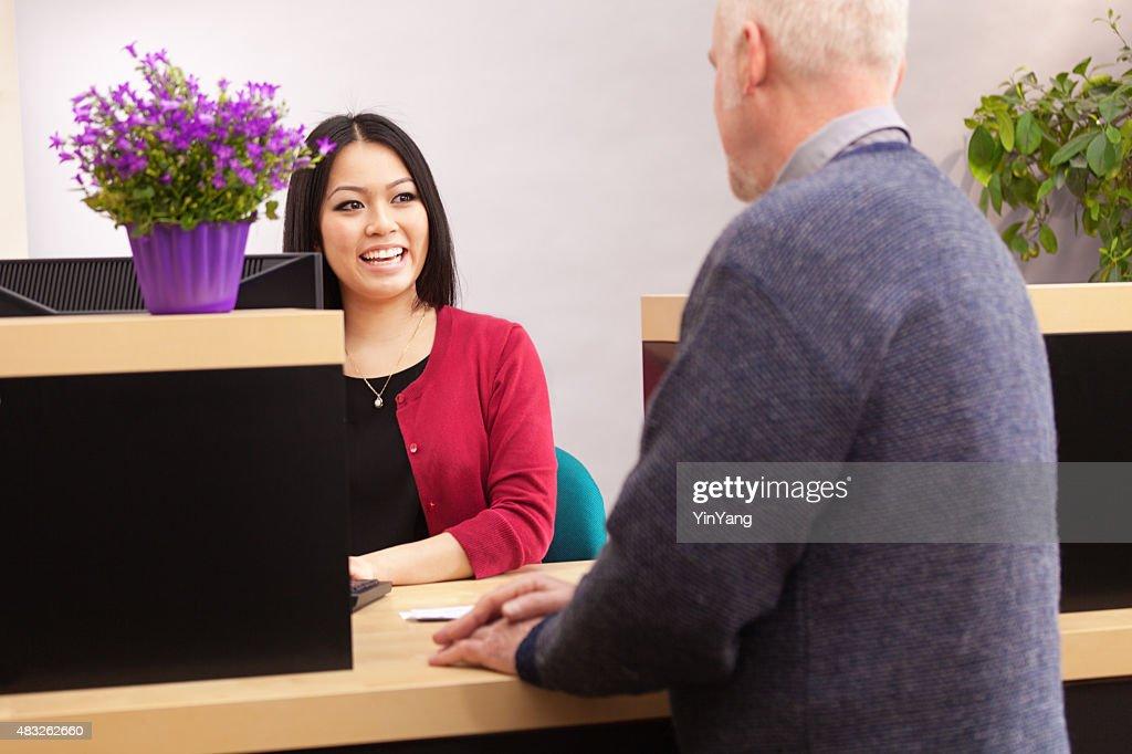 Bank Teller Serving Customer Over Retail Banking Service ...