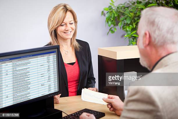 Bank Teller Serving Customer Over Retail Banking Service Counter