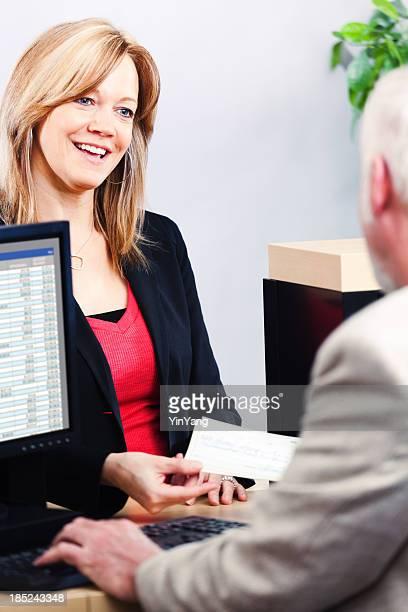 Bank Teller Serving Woman Customer's Finances at Retail Banking Counter